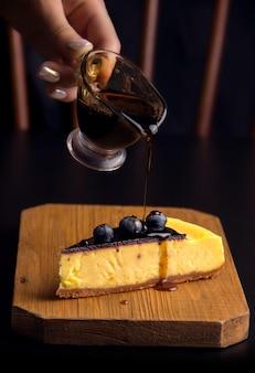 어두운 배경에 소스를 뿌린 블루베리를 곁들인 디저트 치즈 케이크