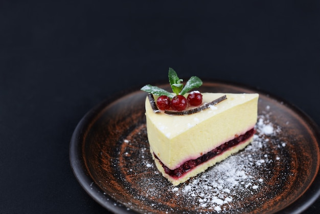 Dessert cheesecake with mint and berries on a black with flowers