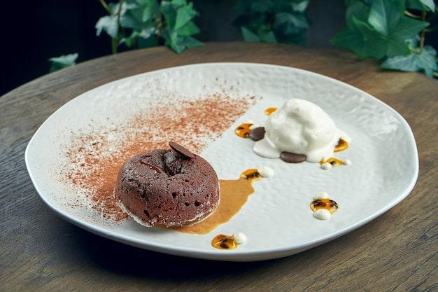 Dessert - chocolate fondant with white ice cream and chia in a white plate