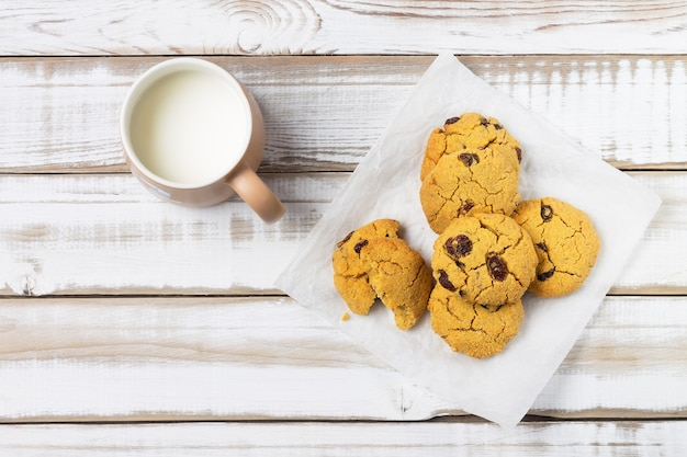 コーンスターチとレーズンで作られたデザートクッキー、木製の背景にミルクのカップ