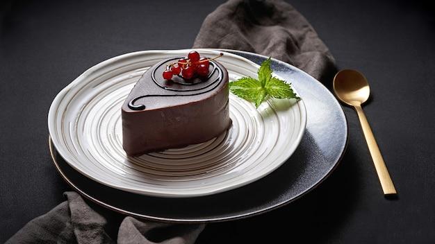 Десерт в шоколадной глазури с красной смородиной и мятой на бело-серых тарелках