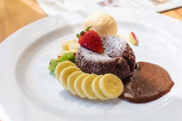A dessert dish call chocolate lava include vanilla ice cream banana kiwi and apple
