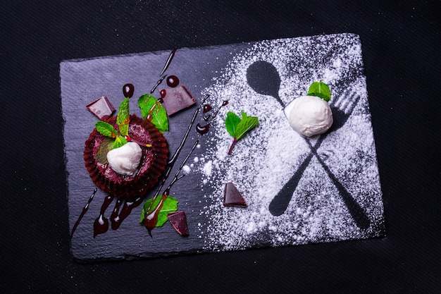 Dessert fondan chocolate with mint and ice cream on a wooden bacground. exquisite french chocolate dessert fondan. cupcakes with decorations for valentines day