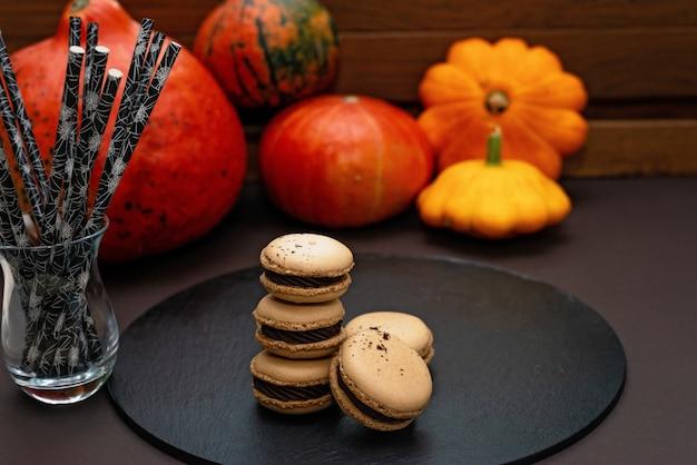 할로윈을 위한 디저트. 추수감사절 메뉴. 프랑스 마카롱. 호박과 에코 칵테일 빨대와 검은 배경에 초콜릿 마카롱. 부드러운 선택적 초점입니다.