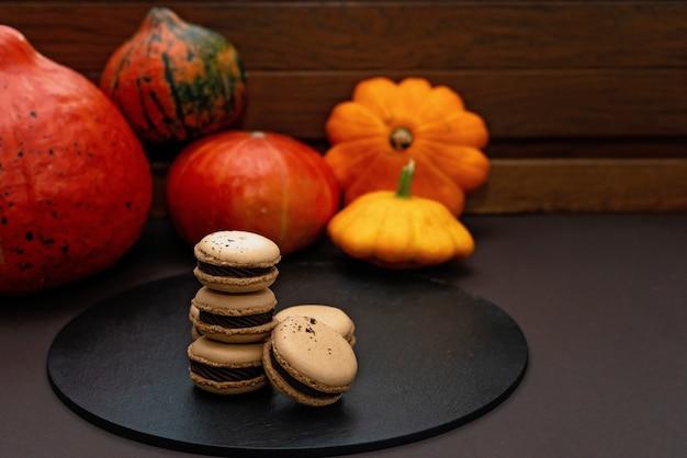 할로윈을 위한 디저트. 추수감사절 메뉴. 프랑스 마카롱. 호박과 검은 배경에 초콜릿 마카롱. 부드러운 선택적 초점입니다. 공간을 복사합니다.