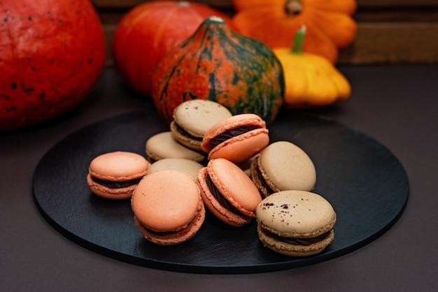할로윈을 위한 디저트. 추수감사절 메뉴. 프랑스 마카롱. 호박과 검은 배경에 대해 돌 과자 보드에 초콜릿과 마카롱. 부드러운 선택적 초점입니다.