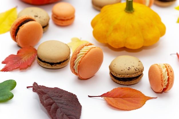 할로윈을 위한 디저트. 추수감사절 메뉴. 프랑스 과자 마카롱. 호박과 단풍이 있는 흰색 배경에 초콜릿과 마스카포네가 있는 마카롱 케이크. 부드러운 선택적 초점입니다. 확대