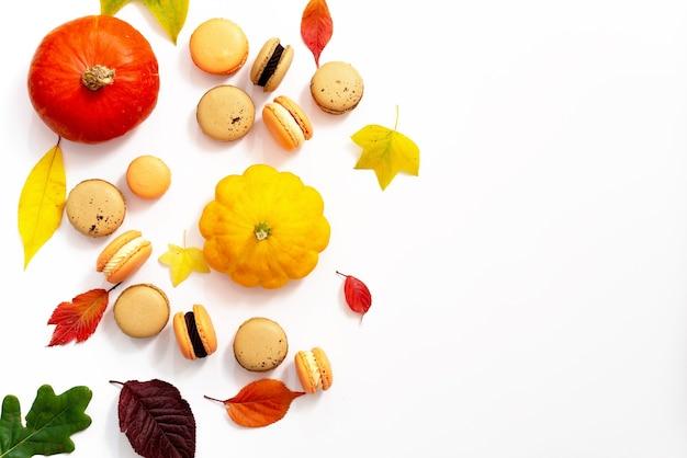 할로윈을 위한 디저트. 추수감사절 메뉴. 프랑스 과자 마카롱. 호박과 단풍이 있는 흰색 배경에 초콜릿과 마스카포네가 있는 마카롱 케이크. 부드러운 선택적 초점입니다. 복사 공간