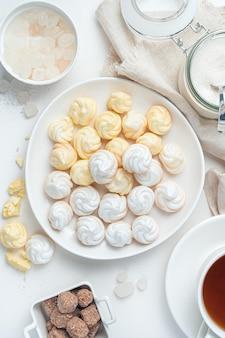 Десертные французские безе на светлом фоне. понятие о кондитерских изделиях. вид сверху.