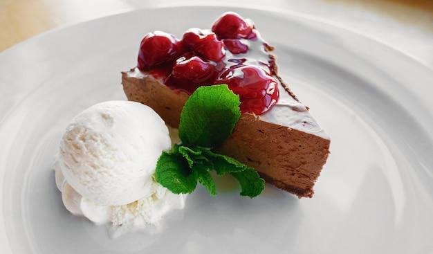Десертное мороженое, шоколадный торт, вишня и мята в кафе