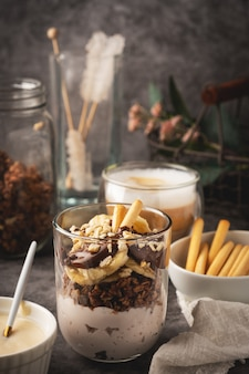 クッキー、カプチーノコーヒーとヨーグルト、グラノーラ、バナナ、チョコレートのガラスのデザート。