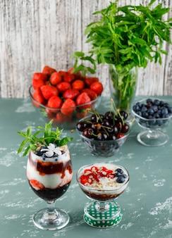 Десерт в вазе и бокале с клубникой, черникой, мятой, вишней под высоким углом на штукатурке и шероховатой поверхности