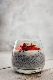 灰色の背景のガラスにチアシードとイチゴを入れた乳糖を含まないミルクで作られたデザート。クリーンフード、デトックス、減量のコンセプト。低炭水化物ダイエットのレシピ。