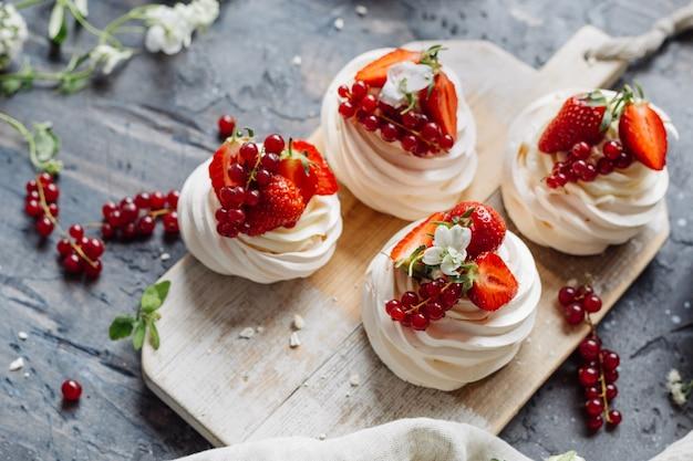 Десертное безе с ягодами на деревянной доске