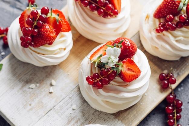 Десертное безе с ягодами на деревянной доске.