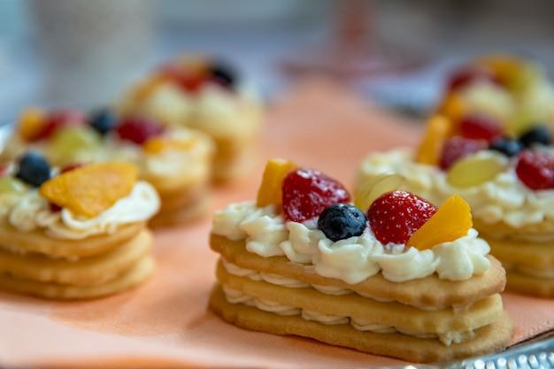 Десерт из кремового печенья и фруктов на праздничном столе.