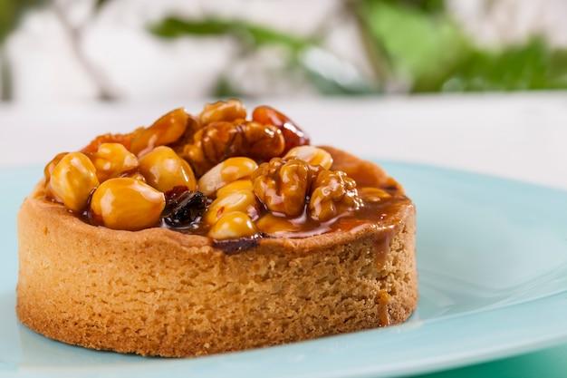Десерт из теста, тарталетки с начинкой из лесных орехов, арахиса и грецких орехов и сухофруктов из слив и абрикосов, ореховые тарталетки, покрытые слоем сахарной карамели.