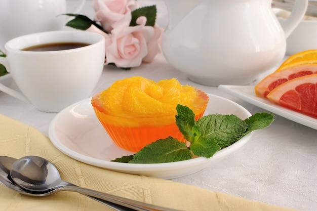 커피 한 잔과 함께 신선한 오렌지 조각을 곁들인 오렌지 젤리 디저트