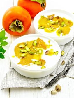 ヨーグルト、柿、蜂蜜のデザート、バニラ、カルダモン、ピスタチオの2つのボウルにタオル、ミント、スプーンを木の板の背景に Premium写真