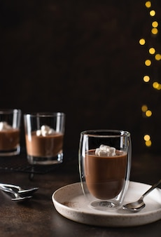Dessert panna cotta in a double wall glass, decorated with marshmallows blurred christmas surface