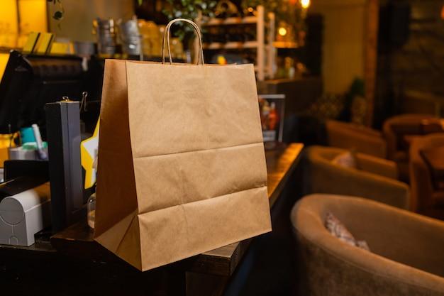 モダンなカフェコーヒーショップフードデリバリーカフェレストのカウンターでお客様を待っているデザートペーパーバッグ...