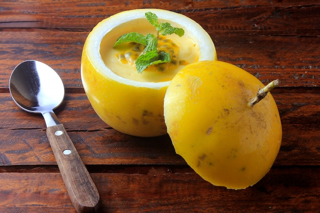 Dessert passion fruit mousse in the peel of fruit on rustic wooden table