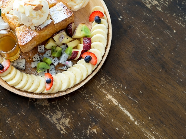 Dessert plate of butter toast with vanilla ice cream, mix fruits, banana slices