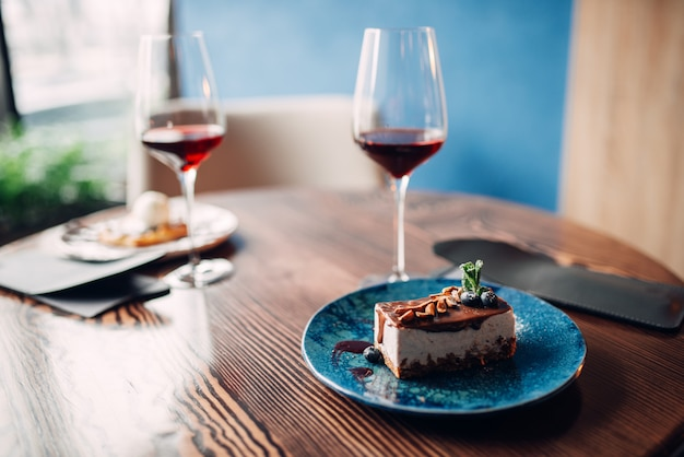 Dessert on plate and red wine in glass, nobody
