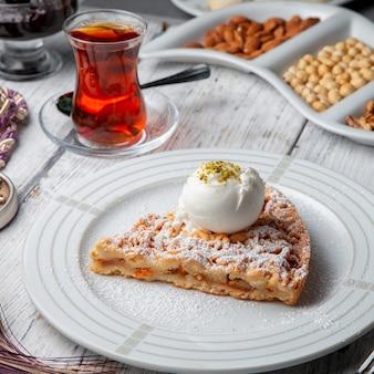 Dessert in un piatto con tè, vista matta dell'angolo alto su un fondo di legno bianco