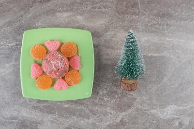 Десертное блюдо и фигурка дерева на мраморной поверхности