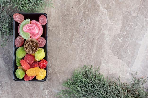 Десертное блюдо и кипарисовые ветви на мраморе.