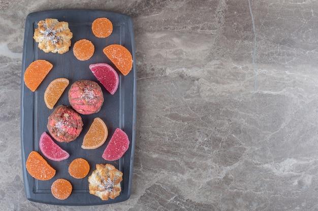 Preparazione del dessert su una tavola marina con marmellate e biscotti su una superficie di marmo