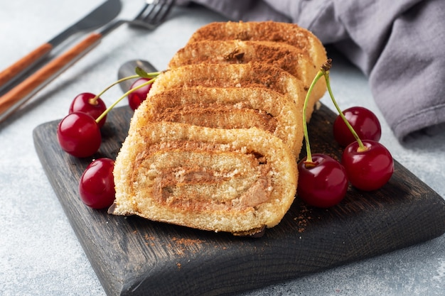 Dessert sponge roll with chocolate cream with cherries on a wooden cutting board.