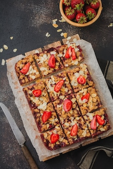 Dessert squares with strawberries and oat streisel on dark old baking tray concrete surface
