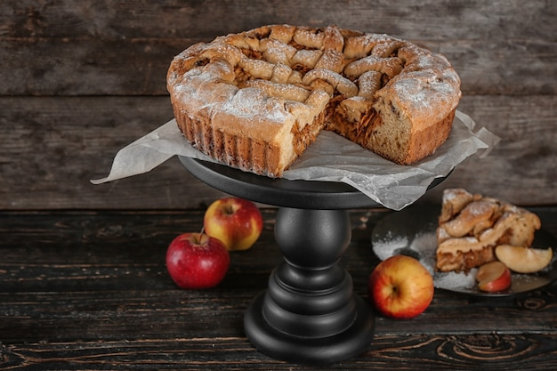 Dessert stand with delicious apple pie on wooden table