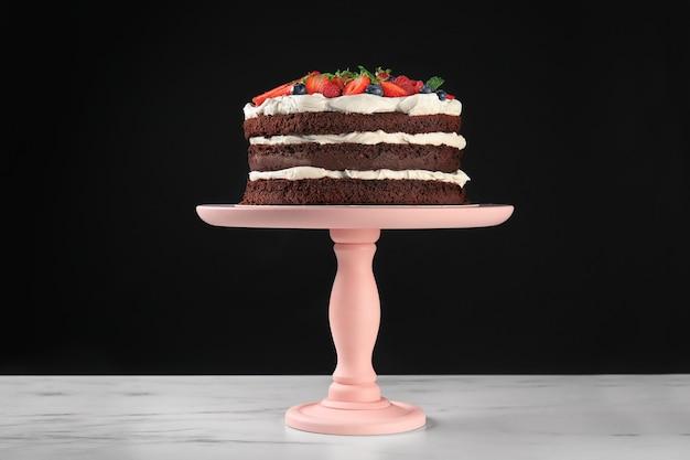 Десертная подставка с вкусным шоколадным тортом на столе на черном фоне