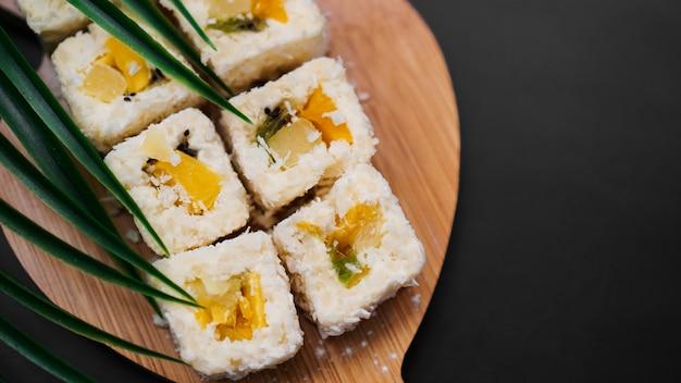 デザート寿司。甘いキウイ、パイナップル、バナナの巻き寿司。黒いテーブルの上の木製トレイの寿司