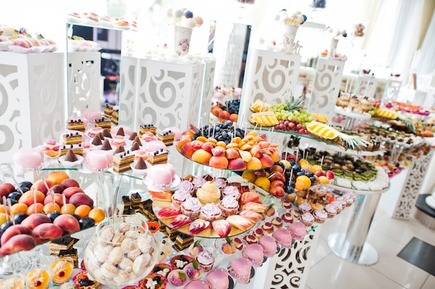 Dessert table of delicious sweets on wedding reception.