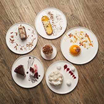 Десертный стол с кексом, муссом, печеньем, чизкейком. кусок торта на белой тарелке на фоне деревянного стола