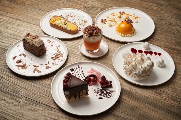 컵 케이크, 무스, 비스킷, 치즈 케이크가있는 디저트 테이블. 나무 테이블 배경에 흰색 접시에 케이크 조각