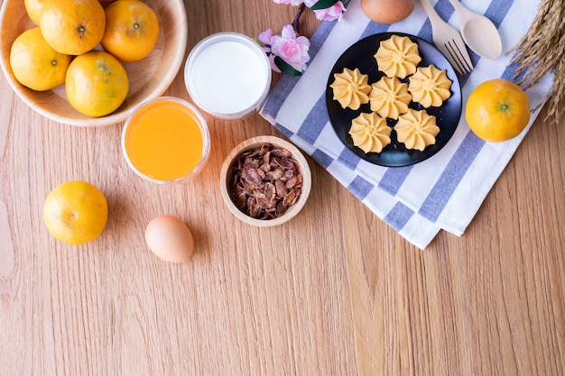 Dessert table with orange juice, glass of milk with healthy food on wood table, copy space.