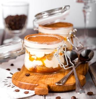 Dessert tiramisu in a jar with sea-buckthorn puree