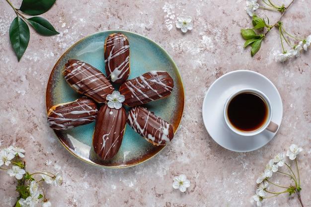 伝統的なフランスのdessert.topビューの内部にカスタードが入ったブラックチョコレートとホワイトチョコレートのエクレアまたはプロフィットロール。