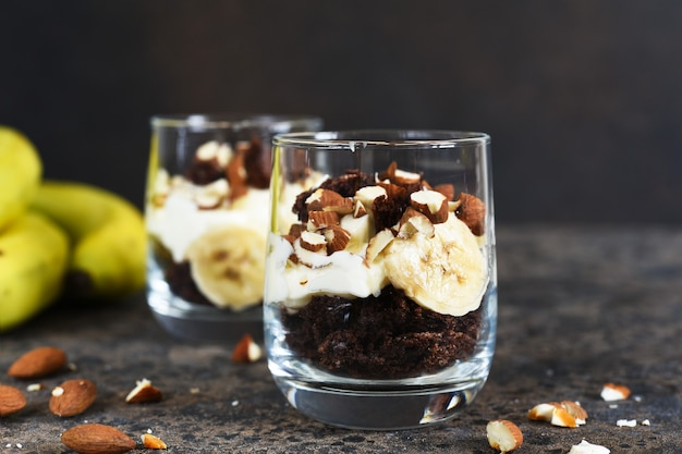 Dessert trifle with banana, chocolate biscuit and cream cheese.