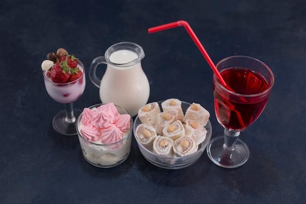 Varietà di dessert con un bicchiere di vino rosso, vista angolare
