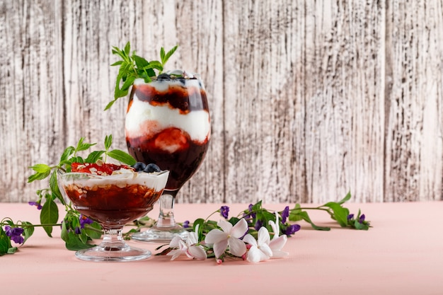 Dessert in vase and goblet with strawberries, blueberries, nuts, mint, flower branches side view on pink and grungy surface
