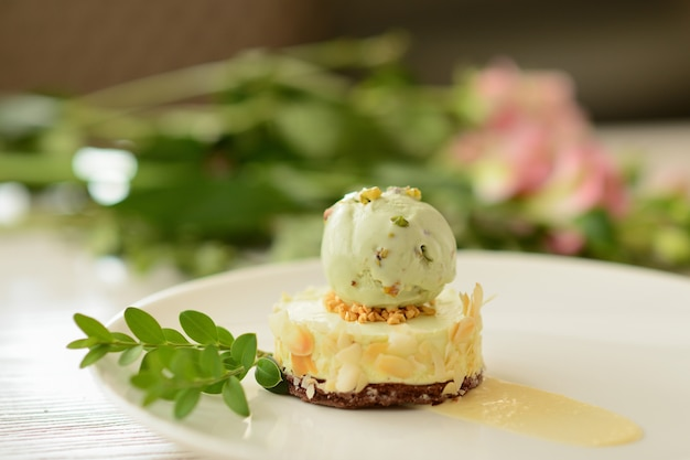 Dessert with a ball of pistachio ice cream with flower decor