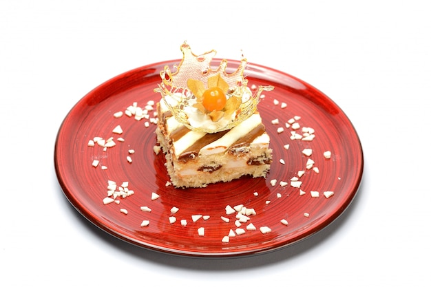 Dessert with caramel and biscuit in a red plate