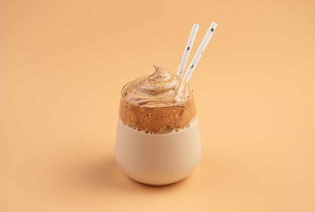 Десерт с кофе и молоком на оранжевой стене. кофе далгона со взбитой кофейной пеной.