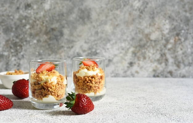 Dessert with crumbs, cream and strawberries. cheesecake in a glass.